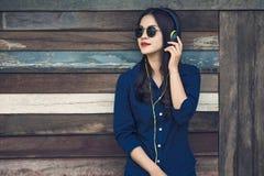 Lycklig asiatisk kvinna som lyssnar till musik på hennes headphone och holdin Arkivfoton