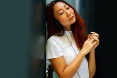 Lycklig asiatisk kvinna som lyssnar till musik på hennes headphone och rymmer smartphonen, livsstilbegrepp royaltyfri fotografi