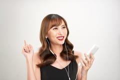 Lycklig asiatisk kvinna som lyssnar till musik p? h?rlurar Ung ny asiatisk kvinnlig modell fotografering för bildbyråer