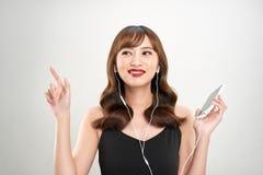 Lycklig asiatisk kvinna som lyssnar till musik p? h?rlurar Ung ny asiatisk kvinnlig modell arkivfoton