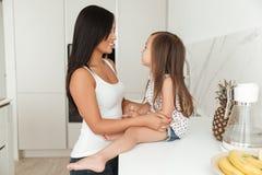 Lycklig asiatisk kvinnamatlagning med hennes lilla dotter tillsammans Arkivfoton