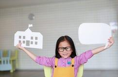Lycklig asiatisk liten flicka i rosa f?rg-guling grova bomullstwillar som rymmer modellpappersskola och den tomma tomma anf?rande royaltyfri fotografi