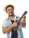 Lycklig asiatisk man som spelar ukuleleisolatbakgrund Arkivfoton