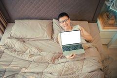 Lycklig asiatisk man som visar en bärbar dator för tom skärm och ligger på säng arkivfoton