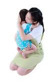 Lycklig asiatisk moder som bär hennes dotter Isolerat på vitbaksida Arkivfoto