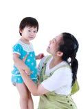 Lycklig asiatisk moder som bär hennes dotter Isolerat på vitbaksida Royaltyfri Foto