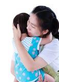 Lycklig asiatisk moder som bär hennes dotter Isolerat på vitbaksida Arkivfoton