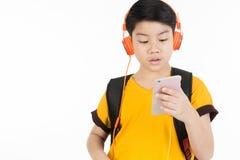 Lycklig asiatisk pojke som använder mobiltelefonen Fotografering för Bildbyråer