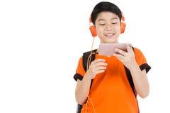 Lycklig asiatisk pojke som använder mobiltelefonen Arkivfoton