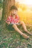 Lycklig asiatisk pojke som ler och rymmer en bok books isolerat gammalt för begrepp utbildning V Royaltyfri Bild
