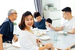 Lycklig asiatisk storfamilj som har matställen hemma mycket av lycka och leenden royaltyfri foto