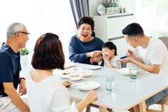 Lycklig asiatisk storfamilj som har matställen hemma mycket av skrattet och lycka fotografering för bildbyråer