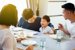 Lycklig asiatisk storfamilj som har matställen hemma mycket av skrattet och lycka arkivfoto