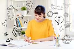 Lycklig asiatisk student för ung kvinna som hemma lär royaltyfria foton
