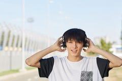Lycklig asiatisk student i hörlurar på en gatabakgrund Tonårigt stilbegrepp kopiera avstånd royaltyfria bilder