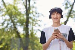 Lycklig asiatisk student i hörlurar på en gatabakgrund Tonårigt stilbegrepp kopiera avstånd arkivbilder