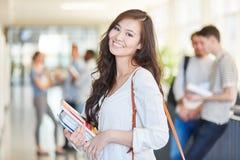 Lycklig asiatisk student i uni royaltyfria foton