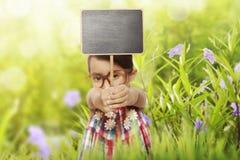 Lycklig asiatisk svart tavla för liten flickainnehavmellanrum arkivfoto