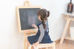 Lycklig asiatisk tecknad film för flickaungeattraktion med krita på svart tavla Fotografering för Bildbyråer