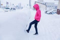 Lycklig asiatisk tonåring i ljust rosa färgomslag som tycker sig om lek Fotografering för Bildbyråer