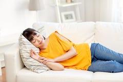 Lycklig asiatisk tonårs- flicka som hemma sover på soffan Arkivbilder
