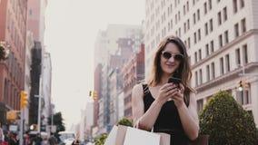 Lycklig attraktiv Caucasian affärskvinna med shoppingpåsar som pratar med vänner på smartphonesamkvämmen app i New York arkivfilmer