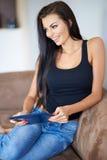 Lycklig attraktiv kvinna som kopplar av med enPC Royaltyfri Foto
