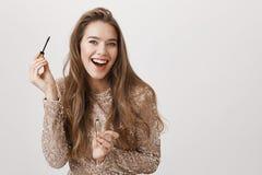 Lycklig attraktiv kvinnlig kvinna som i huvudsak ler, medan se kameran som, om det är spegeln och att sätta på mascara Royaltyfri Fotografi