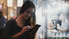 Lycklig attraktiv kvinnlig vd genom att använda försäljaren för mat för gata för smartphonee-kommers app den near ånga i aftonen  arkivfilmer