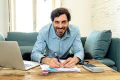 Lycklig attraktiv latinsk man som hem beräknar finanser arkivfoto