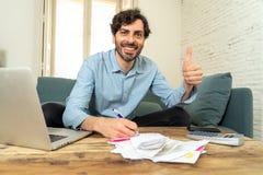 Lycklig attraktiv latinsk man som hem beräknar finanser royaltyfri bild