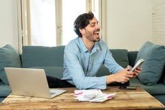 Lycklig attraktiv latinsk man som hem beräknar finanser royaltyfria foton