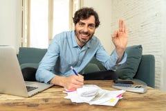 Lycklig attraktiv latinsk man som hem beräknar finanser fotografering för bildbyråer
