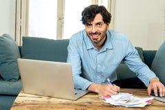 Lycklig attraktiv latinsk man som hem beräknar finanser royaltyfria bilder