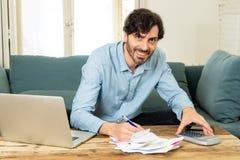 Lycklig attraktiv latinsk man som hem beräknar finanser arkivfoton