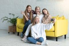 Lycklig attraktiv lesbisk familj i tillf?llig kl?der som g?r selfie, medan sitta p? den gula soffan hemma, blond daughtet arkivbild
