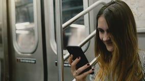 Lycklig attraktiv millennial freelancerflicka som sitter i gångtunneldrev genom att använda sociala nätverk på appen och att le f stock video