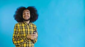 Lycklig attraktiv ung Afro--amerikan man som använder telefonen och får goda nyheter på blå bakgrund Begrepp av sinnesr?relser arkivfilmer