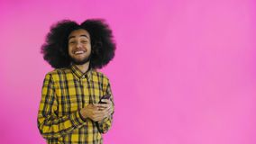 Lycklig attraktiv ung Afro--amerikan man som använder telefonen och får goda nyheter på purpurfärgad bakgrund Begrepp av sinnesr? stock video