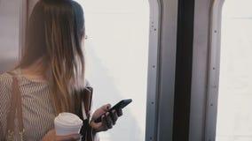 Lycklig avkopplad attraktiv kvinnlig millennial flicka i ett gångtunneldrev som ser smartphonen genom att använda budbäraren på i arkivfilmer