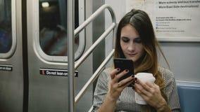 Lycklig avkopplad attraktiv millennial flicka som direktanslutet sitter i hållande ögonen på video för gångtunneldrev på appen oc lager videofilmer