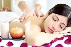 Lycklig avkopplad kvinna som får tillbaka massage i lyxig brunnsort arkivbild