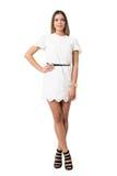 Lycklig avkopplad modeskönhet snör åt in den vita klänningen som poserar på kameran Arkivbild