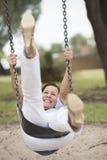 Lycklig avkopplad mogen kvinna på utomhus- gunga Arkivfoto