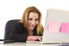 Lycklig avkopplad 40-talaffärskvinna som ler säkert arbete på varven Arkivfoto