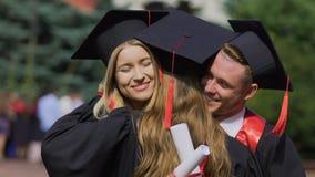 Lycklig avläggande av examendag studenter som kramar och att gratulera sig, bästa vän arkivfilmer
