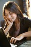 lycklig bärbar dator genom att använda kvinnan fotografering för bildbyråer