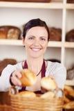 Lycklig bageriarbetare som säljer nya rullar Arkivfoton