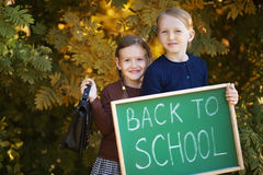 Lycklig baksida för två lilla systrar till skolan Fotografering för Bildbyråer