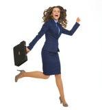 Lycklig banhoppning för affärskvinna med portföljen royaltyfria foton